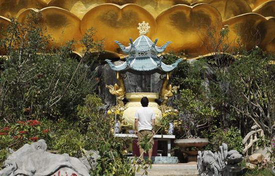 Andrei Verner standing beneath the Big Golden Buddha statue in Da Lat, Vietnam